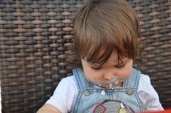 Το κορίτσι μικρών παιδιών τρώει στον υπαίθριο καφέ στοκ εικόνες