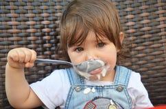 Το κορίτσι μικρών παιδιών τρώει στον υπαίθριο καφέ στοκ εικόνες με δικαίωμα ελεύθερης χρήσης