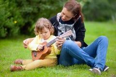 Το κορίτσι μικρών παιδιών Talanted μαθαίνει να παίζει ukulele την κιθάρα στοκ φωτογραφίες με δικαίωμα ελεύθερης χρήσης