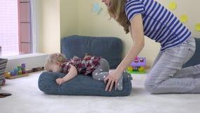 Το κορίτσι μικρών παιδιών αναρριχείται στο μπλε τεράστιο μαξιλάρι και το ωθώντας μαξιλάρι μητέρων της στο πάτωμα απόθεμα βίντεο