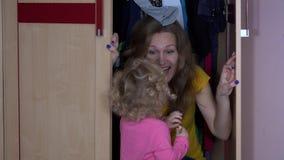 Το κορίτσι μικρών παιδιών βρίσκει τη μητέρα της στο ντουλάπι Ευτυχές παιδικό παιχνίδι με το mom απόθεμα βίντεο