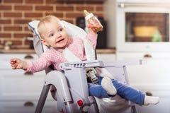 Το κορίτσι μικρών παιδιών ενός έτους κάθεται στην υψηλή καρέκλα μωρών με τη σίτιση του μπουκαλιού στο χέρι της Στοκ Φωτογραφία