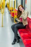 Το κορίτσι μιλά σε ένα τηλέφωνο κυττάρων μέσα σε ένα κενό υπόγειο τρένο Στοκ φωτογραφία με δικαίωμα ελεύθερης χρήσης