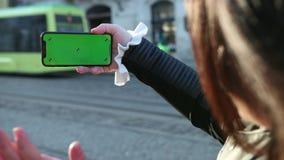 Το κορίτσι μιλά σε ένα smartphone του τηλεφώνου Κύματα το χέρι στους ανθρώπους που βλέπουν στην οθόνη απόθεμα βίντεο