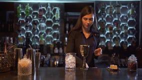 Το κορίτσι μπάρμαν με τη μακριά καφετιά τρίχα έβαλε πολλούς κύβους του πάγου σε ένα γυαλί και ένα μεγάλο κομμάτι του πάγου στο απ απόθεμα βίντεο