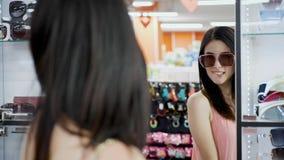 Το κορίτσι μπροστά από τον καθρέφτη προσπαθεί στα γυαλιά ηλίου απόθεμα βίντεο