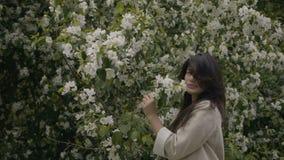 Το κορίτσι μυρίζει το δέντρο μηλιάς φιλμ μικρού μήκους