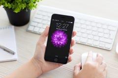 Το κορίτσι ξεκλειδώνει το iPhone 6 διαστημικός γκρίζος πέρα από τον πίνακα Στοκ Φωτογραφία