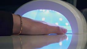 Το κορίτσι ξεραίνει τη στιλβωτική ουσία καρφιών στη UV ξήρανση απόθεμα βίντεο