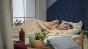 Το κορίτσι ξυπνά και κρύβει κάτω από τις καλύψεις στοκ φωτογραφία