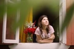 Το κορίτσι ξυπνήστε το θερινό πρωί κοιτάζει από το παράθυρο Στοκ Εικόνες