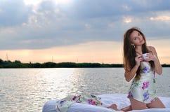 Το κορίτσι ξύπνησε σε ένα κρεβάτι στο φλιτζάνι του καφέ νερού και ποτών. στοκ φωτογραφία με δικαίωμα ελεύθερης χρήσης