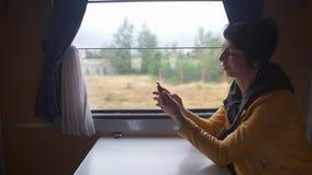 Το κορίτσι οδηγά ένα τραίνο από το παράθυρο, χρησιμοποιεί το τηλέφωνο φιλμ μικρού μήκους