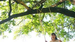 Το κορίτσι οδηγά στην ταλάντευση στο πάρκο πόλεων και χαμογελά στο έντονο φως του ηλιοβασιλέματος φιλμ μικρού μήκους