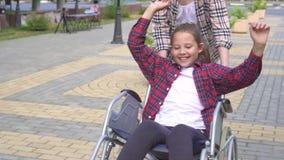 Το κορίτσι οδηγά τον ευτυχή έφηβο στην αναπηρική καρέκλα στο θερινό πάρκο Αργό MO απόθεμα βίντεο