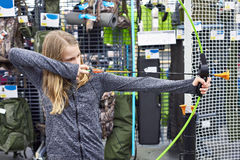 Το κορίτσι δοκιμάζει το τόξο παιδιών ` s στο αθλητικό κατάστημα Στοκ Εικόνες