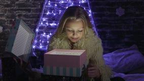 Το κορίτσι ομορφιάς ανοίγει το κιβώτιο δώρων Χριστουγέννων με τα φω'τα θαύματος Έκπληκτη γυναίκα που παίρνει το μαγικό δώρο απόθεμα βίντεο