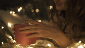 Το κορίτσι ομορφιάς με τις κυρτές τρίχες ανοίγει το κιβώτιο δώρων Χριστουγέννων Φω'τα υποβάθρου Bokeh απόθεμα βίντεο