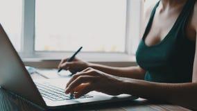 Το κορίτσι ο σχεδιαστής εργάζεται στον υπολογιστή και επισύρει την προσοχή σε μια ταμπλέτα γραφικής παράστασης απόθεμα βίντεο