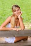 το κορίτσι πάγκων κάθεται Στοκ Εικόνα