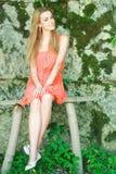 το κορίτσι πάγκων συμπαθητικό κάθεται ξύλινο στοκ φωτογραφία