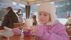 Το κορίτσι πίνει το καυτό τσάι ή τα κοκτέιλ στο άνετο χιονώδες σπίτι καλλιεργούν στο χειμερινό πρωί φιλμ μικρού μήκους