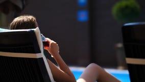 Το κορίτσι πίνει το κρασί ή το χυμό σε έναν αργόσχολο κοντά σε μια πισίνα απόθεμα βίντεο