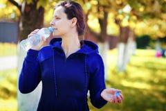 Το κορίτσι πίνει το νερό από το μπουκάλι στο χρυσό πάρκο φθινοπώρου η γυναίκα πίνει το νερό μετά από να ασκήσει τη γιόγκα στο πάρ Στοκ Εικόνες