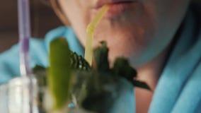 Το κορίτσι πίνει το οινοπνευματώδες ποτό mojito με τη μέντα και τον ασβέστη Κινηματογράφηση σε πρώτο πλάνο ενός γυαλιού με το moj φιλμ μικρού μήκους