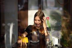 Το κορίτσι πίνει τον καφέ και προσέχει το βίντεο στο κινητό τηλέφωνο στοκ εικόνες με δικαίωμα ελεύθερης χρήσης
