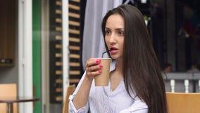 Το κορίτσι πίνει τον καφέ με ένα άχυρο σε έναν υπαίθριο καφέ απόθεμα βίντεο
