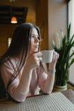 Το κορίτσι πίνει τον καφέ σε έναν καφέ στοκ φωτογραφίες με δικαίωμα ελεύθερης χρήσης