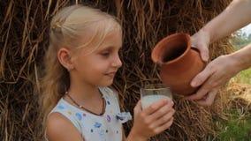 Το κορίτσι πίνει το γάλα αγελάδων ` s από ένα ποτήρι ενάντια στο σκηνικό μιας θυμωνιάς χόρτου σε ένα αγρόκτημα φιλμ μικρού μήκους