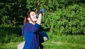Το κορίτσι πίνει το νερό κατά τη διάρκεια του workout Στοκ Φωτογραφίες