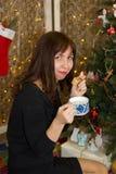 Το κορίτσι πίνει το τσάι από ένα διακοσμημένο φλυτζάνι χριστουγεννιάτικο δέντρο Στοκ Εικόνες