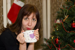 Το κορίτσι πίνει το τσάι από ένα διακοσμημένο φλυτζάνι χριστουγεννιάτικο δέντρο Στοκ Εικόνα