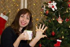 Το κορίτσι πίνει το τσάι από ένα διακοσμημένο φλυτζάνι χριστουγεννιάτικο δέντρο Στοκ Φωτογραφία