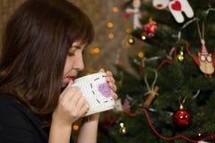 Το κορίτσι πίνει το τσάι από ένα διακοσμημένο φλυτζάνι χριστουγεννιάτικο δέντρο Στοκ εικόνα με δικαίωμα ελεύθερης χρήσης