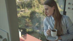 Το κορίτσι πίνει το τσάι από το παράθυρο του καθιερώνοντος τη μόδα εστιατορίου απόθεμα βίντεο