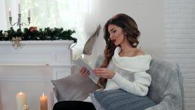 Το κορίτσι πίνει το τσάι στο καθιστικό, διαβάζοντας μια συνεδρίαση βιβλίων στον καναπέ από την εστία με τα κεριά, Παραμονή Πρωτοχ απόθεμα βίντεο