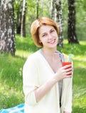 Το κορίτσι πίνει το χυμό Στοκ Φωτογραφία