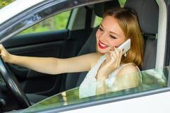 Το κορίτσι πίσω από τη ρόδα ενός αυτοκινήτου που μιλά στο τηλέφωνο Στοκ Εικόνες