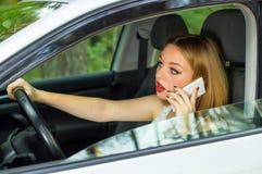 Το κορίτσι πίσω από τη ρόδα ενός αυτοκινήτου που μιλά στο τηλέφωνο Στοκ εικόνα με δικαίωμα ελεύθερης χρήσης