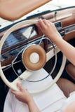 Το κορίτσι πίσω από τη ρόδα ενός όμορφου αναδρομικού αυτοκινήτου Στοκ Εικόνες