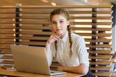 Το κορίτσι πίσω από το lap-top κάθεται στο CAF Στοκ εικόνες με δικαίωμα ελεύθερης χρήσης