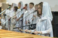 Το κορίτσι παίζει ένα xylophone Άσπρα ενδύματα, χορωδία Στοκ Εικόνες