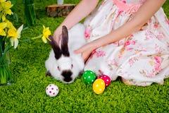 Το κορίτσι παίζει με ένα κουνέλι Πάσχας και τα αυγά Πάσχας Στοκ Φωτογραφίες