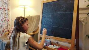 Το κορίτσι παίζει το σχολείο στο σπίτι απόθεμα βίντεο
