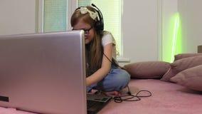 Το κορίτσι παίζει τα παιχνίδια στο lap-top φιλμ μικρού μήκους