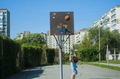 Το κορίτσι παίζει την καλαθοσφαίριση στην οδό Ρίχνει τη σφαίρα στο καλάθι στοκ εικόνες με δικαίωμα ελεύθερης χρήσης